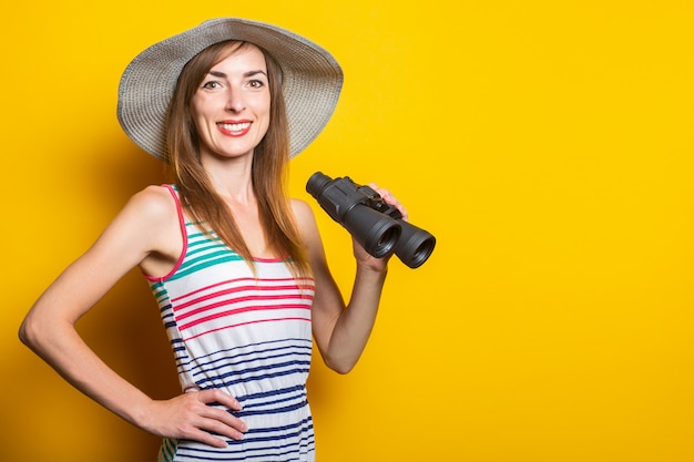 Woman smiling with a hat and a striped dress holding binoculars on a yellow space.