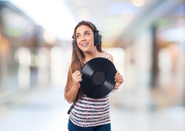 헤드폰 및 비닐 레코드와 함께 웃는 여자