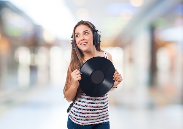 Woman smiling with headphones and a vinyl record