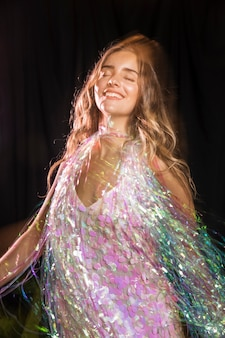 Woman smiling with her eyes closed and wearing a shawl of sparkles