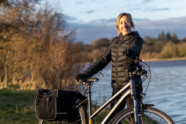 Woman smiling with her touring bike at blessington lakes wicklow ireland
