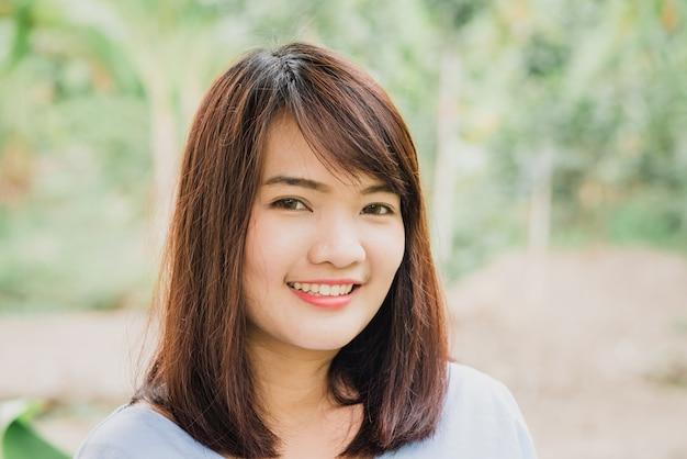 完全な笑顔と白い歯で公園に笑顔とカメラを見ている女性
