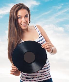 Donna sorridente con un disco in vinile