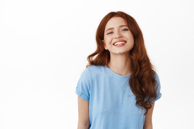 하얀색 완벽한 이빨로 웃고 있는 여성, 행복한 얼굴 감정을 보여주며 흰색 바탕에 캐주얼한 파란색 티셔츠를 입고 서 있는 여성