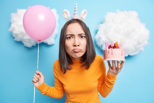 Woman smirks face looks dissatisfied at camera reacts on bad news organises birthday party holds strawberry cake inflated balloon