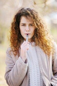 Woman smokes electronic cigarette