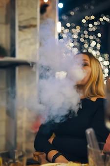 라운지 바에서 물담배를 피우는 여성 검은 드레스를 입은 여성이 바에 있는 카페 테이블 밝은 조명에서 쉬고 있습니다...
