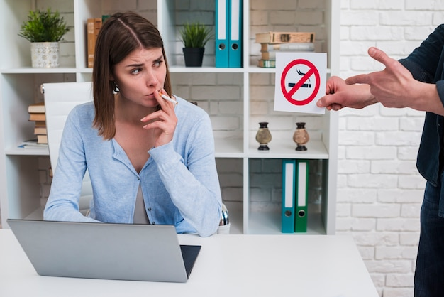 Woman smoking cigarette looking at no smoking sign holding by her male colleague