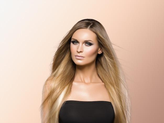 女性の滑らかな髪のブロンドのlond美しさ自然なカジュアルな肖像画。ベージュに。