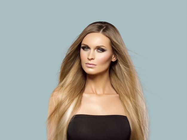 女性の滑らかな髪のブロンドのlond美しさ自然なカジュアルな肖像画。灰色に。