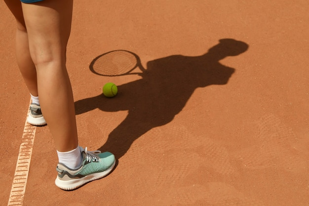 Woman in sneakers on clay court with tennis ball