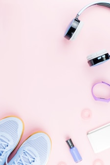Woman sneakers, headphones, fitness tracker and smartphone on pastel pinktable. sport fashion concept. flat lay