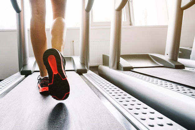 Woman in sneakers running on treadmill