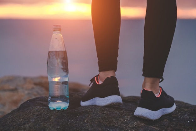 Woman in sneakers standing on a rock next to a bottle of water on a sea background at sunset
