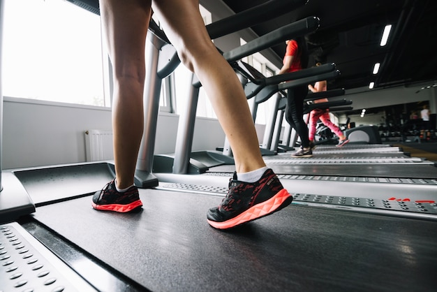 Woman in sneakers walking on treadmill