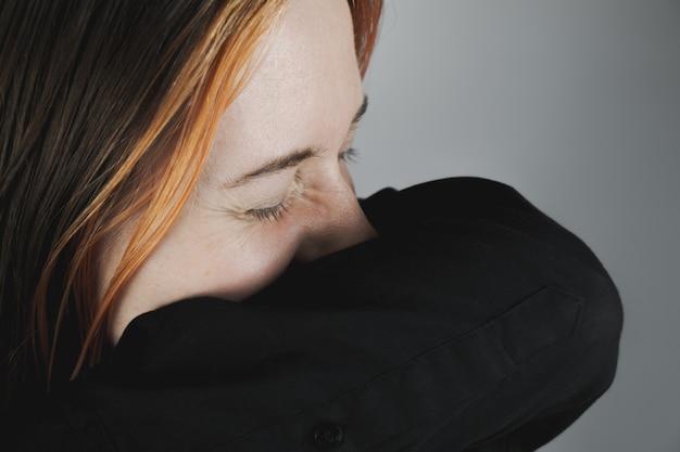 Женщина чихает в рукав - концепция сохранения вируса или инфекции. женщина прикрывает нос и рот руками, пытаясь чихнуть, личной гигиены или здравоохранения