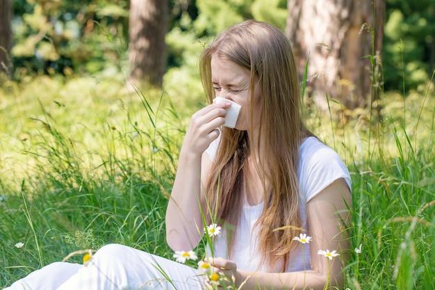 牧草地でくしゃみをする女性