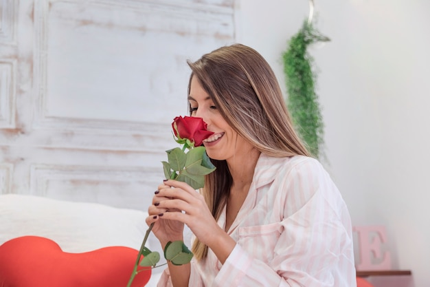 Woman sniffing rose on bed