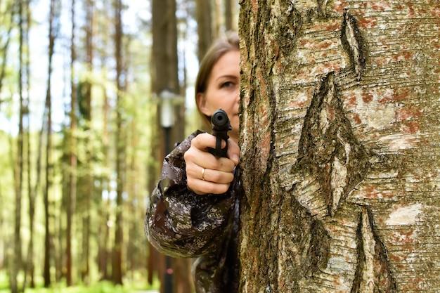 森の中の武器の発砲を持つ女性狙撃兵、木の後ろにキラーの女の子