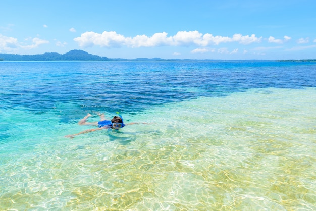 Woman snorkeling in caribbean sea, turquoise blue water, tropical island