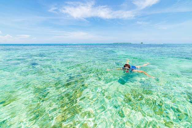 Женщина подводного плавания в карибском бассейне на коралловых рифов тропической бирюзовой водой.