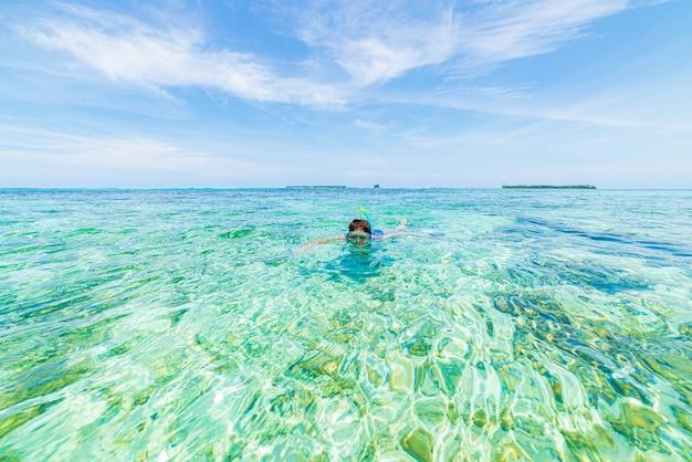 Женщина с маской и трубкой в карибском море, бирюзовой воде, тропическом острове.