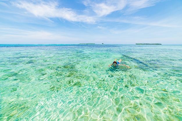 Женщина с маской и трубкой на коралловом рифе тропического карибского моря, бирюзовой голубой воде. индонезия архипелаг вакатоби, морской национальный парк, туристическое направление для дайвинга