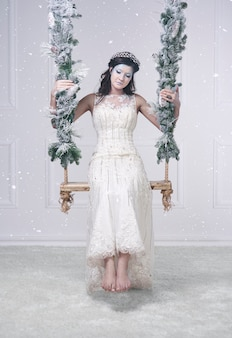 Donna in costume da regina delle nevi sull'altalena