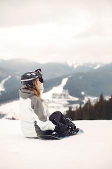 Donna in tuta da snowboard. sportiva su una montagna con uno snowboard in mano all'orizzonte. concetto di sport