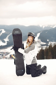 Woman in snowboard suit. sportswoman on a mountain with a snowboard in the hands on the horizon. concept on sports