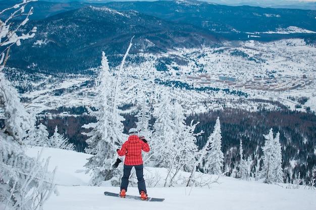 赤いジャケットと白いヘルメットをかぶった女性スノーボーダーがスノーボードの雪山の頂上から降りてきます。素晴らしい冬の風景