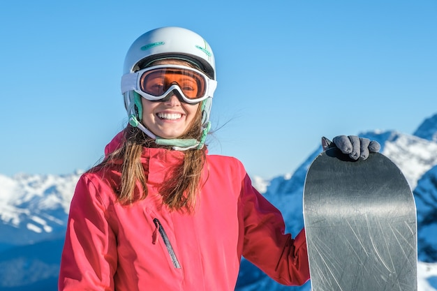 スノーボードで立っている女性スノーボーダー。スキー場の頂上で陽気なスノーボーダーのクローズアップの肖像画
