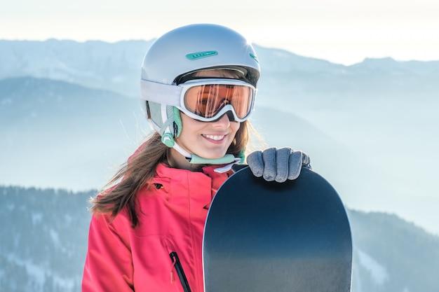 Женщина сноубордист, стоя с сноуборд. портрет крупного плана