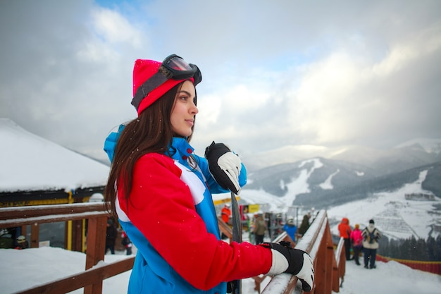 Woman snowboarder in winter at ski resort and sky