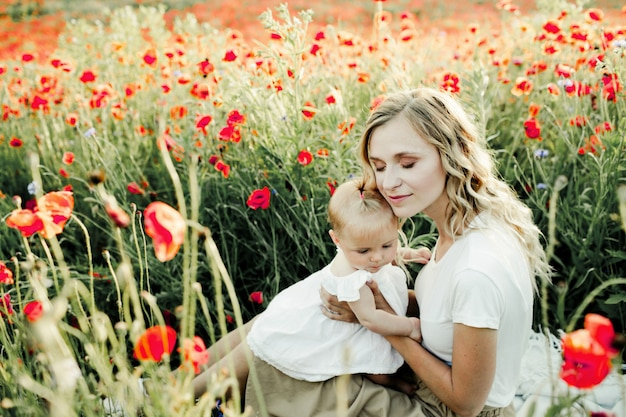 Woman snuggles to her baby on the poppy field