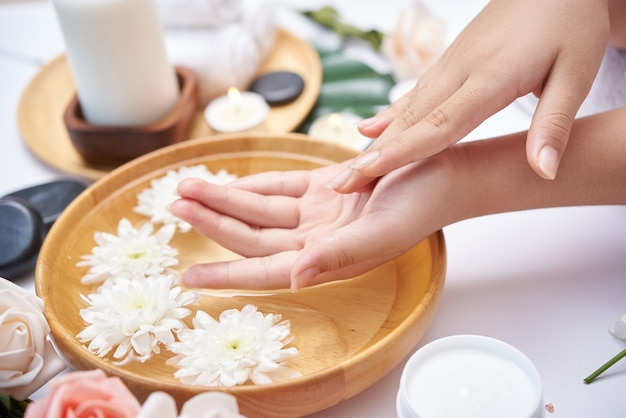 Woman soaking her hands in bowl of water and flowers, spa treatment and product for female feet and hand spa, massage pebble, perfumed flowers water and candles, relaxation. flat lay. top view.