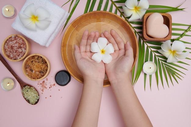 Женщина, замачивающая руки в миске с водой и цветами, спа-процедура и средство для женских ног и спа для рук, массажная галька, ароматизированная цветочная вода и свечи, расслабление. плоская планировка. вид сверху.