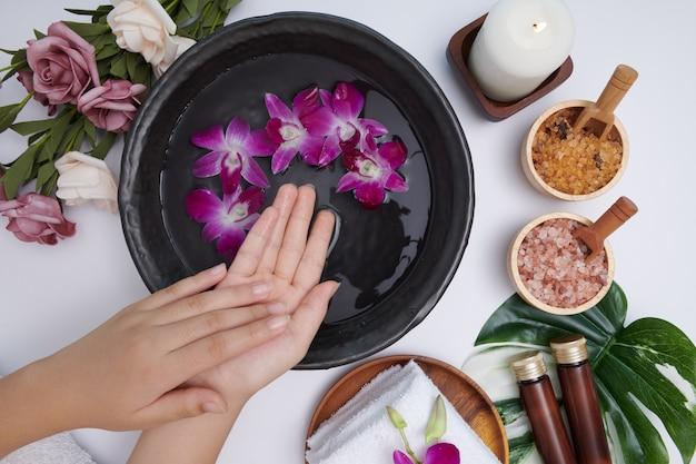 물과 꽃 그릇에 손을 담그는 여성, 여성 피트 및 핸드 스파 용 스파 트리트먼트 및 제품, 마사지 조약돌, 향수 꽃 물과 양초, 휴식. 평평하다. 평면도.