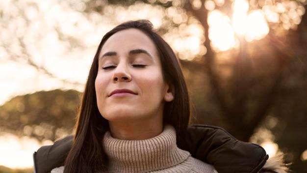 屋外で自然を浴びる女性