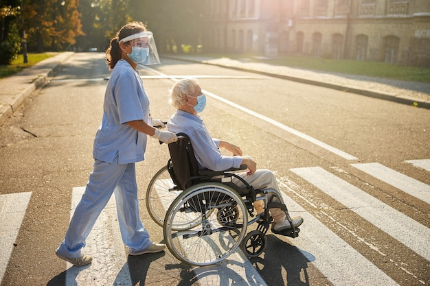 Woman social worker with elderly man walking in the city