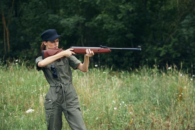 Женщина-солдат он держит пистолет в руках, целится в цель зеленые листья зеленые деревья на фоне
