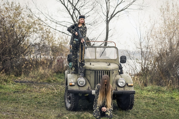 Woman soldier and her hostage against military car