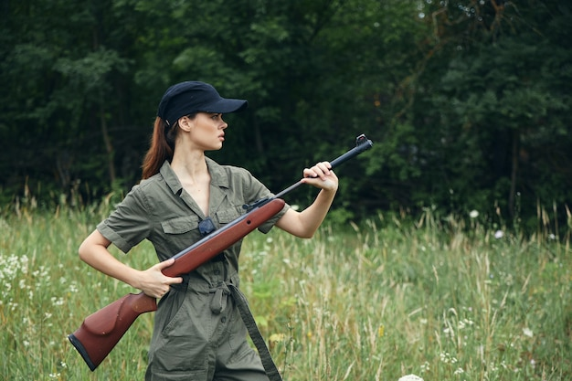 Woman soldier holds a gun in a side view against the background of the forest