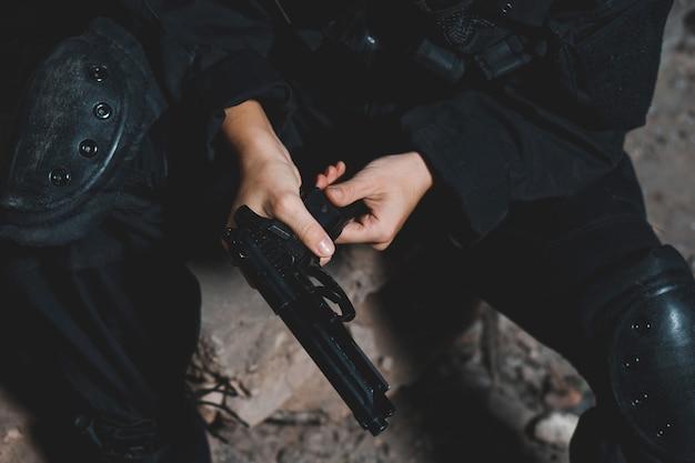Женщина-солдат в черной форме, перезаряжая пистолет
