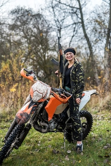Woman soldier posing with rifle and motorcycle