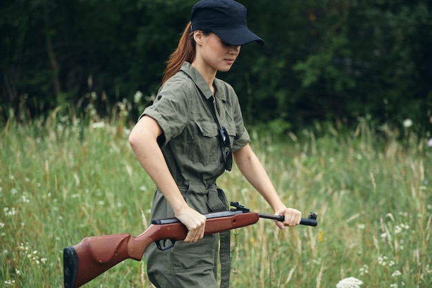 Woman soldier reloading the gun green jumpsuit green leaves forest background
