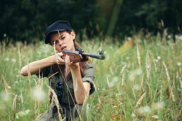여자 군인은 엄폐물에 앉아 그 앞에 총을 들고 무기