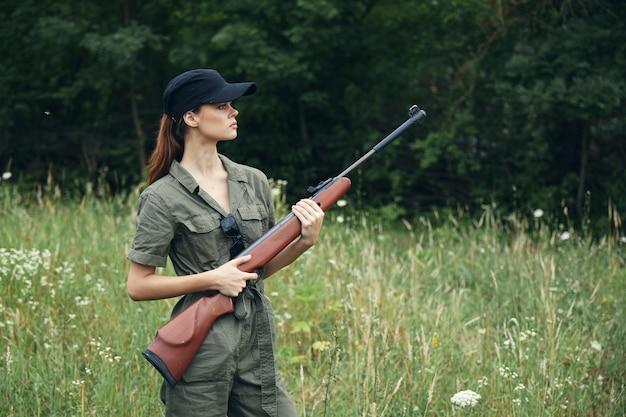 Женщина-солдат с ружьем в руках зеленый комбинезон черная бейсболка зеленые листья обрезанный вид