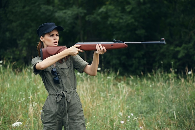 Woman soldier with a gun in hand takes aim green overalls green trees