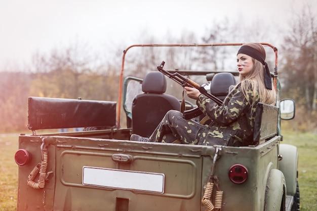 군용 차 근처에서 포즈를 취하는 소총을 가진 여자 군인